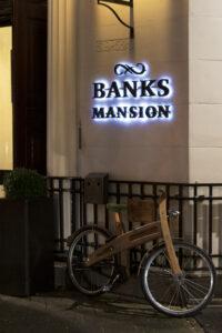 """Ein Fahrrad mit einem hölzernen Rahmen steht angelehnt an einen schwazen Metallzaun vor einem Haus. An dessen Fassade prangt der schwarze Schriftzug """"BANK'S MANSION"""", welcher weiß hinterleuchtet wird."""