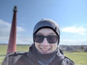 Hendryk im schwarzen Mantel mit grauer Mütze und Sonnenbrille auf einem Damm. Im Hintergrund sieht man grüne Weide und blauen Himmel mit vereinzelten weißen Wolken, sowie links von ihm einen roten Leuchtturm.