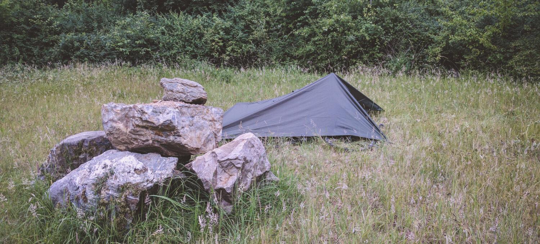 Eine sommerliche Wiese mit teilweise schon vertrocknendem Gras. im Vordergrund sind ein paar Felsquader aufgetürmt, rechts dahinter steht ein mattgrünes Tarp. Im Hintergrund befinden sich ein paar dunkelgrüne Büsche.