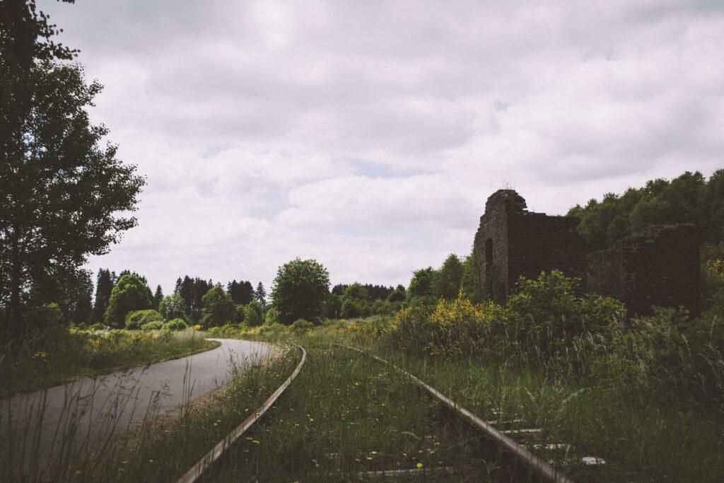Links die Vennbahntrasse als ausgebauter Radweg, mittig die übrig gebliebenen Schienen des zweiten Gleises, rechts davon ein zur Ruine verkommenes Häuschen am Gleis.