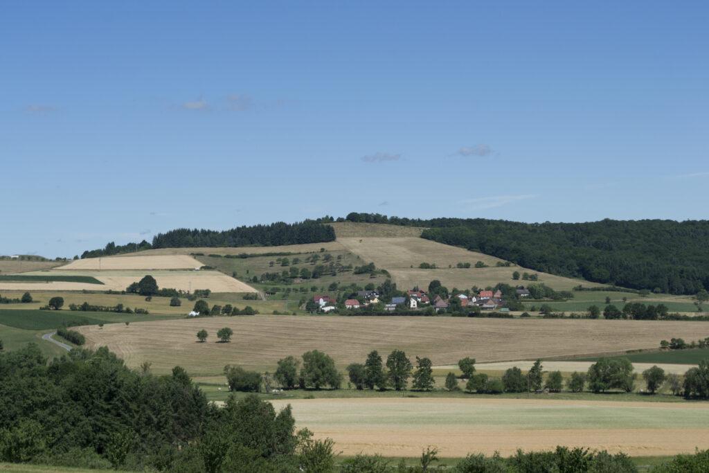 Ein kleines Dorf am Fuße eines teils bewaldeten Hügels. Vor ihm und hinter ihm sind alle Felder schon gemäht, nur ein paar Bäume tragen noch ihre grünen Blätter.