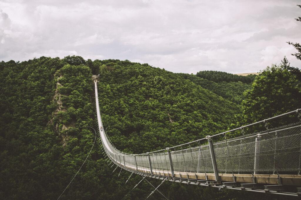 Die Hängeseilbrücke Geierlay über dem bewaldeten Tal, diesmal von der Seite fotografiert. Am rechten Bildrand ist der Einstieg am Felsvorsprung, während die Brücke nach links das Tal überspannt und in der Ferne links das andere Ende zu sehen ist.