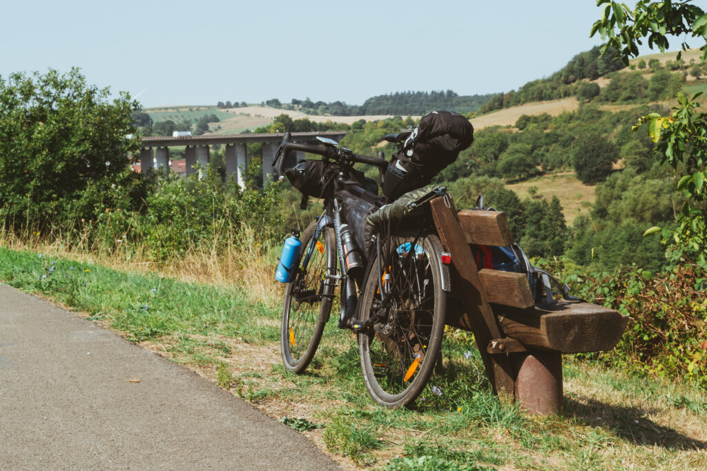 Mein Fahrrad, angelegt an eine Bank am Rande des asphaltierten Weges. Im HIntergrund erstreckt sich eine Brücke mit mehreren Pfeilern über ein Tal. Das Rad ist bepackt mit Lenkerrolle, Rahmentasche, Satteltasche, Tarp und mehreren Flaschen, mein Rucksack steht auf der Bank.