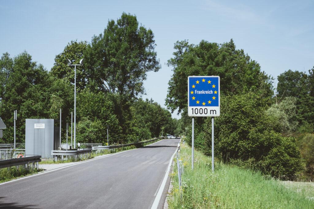 """Eine von Bäumen gesäumte gerade Straße. An ihrem rechten Rand steht auf zwei Pfählen ein rechteckiges Schild. Oben ist ein blaues Quadrat mit einem Kreis aus 12 gelben Sternen, darin befindet sich das Wort """"Frankreich"""". Darunter steht auf weißen Grund in schwarzer Schrift die Aussage """"1000 m""""."""