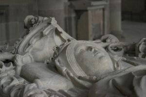 Detailaufnahme des Deckels des Grabmals von Edgitha, Königin des Ostfrankenreichs und Gemahlin von Otto dem Großen, mit Fokus auf den Kopf und den Baldachin