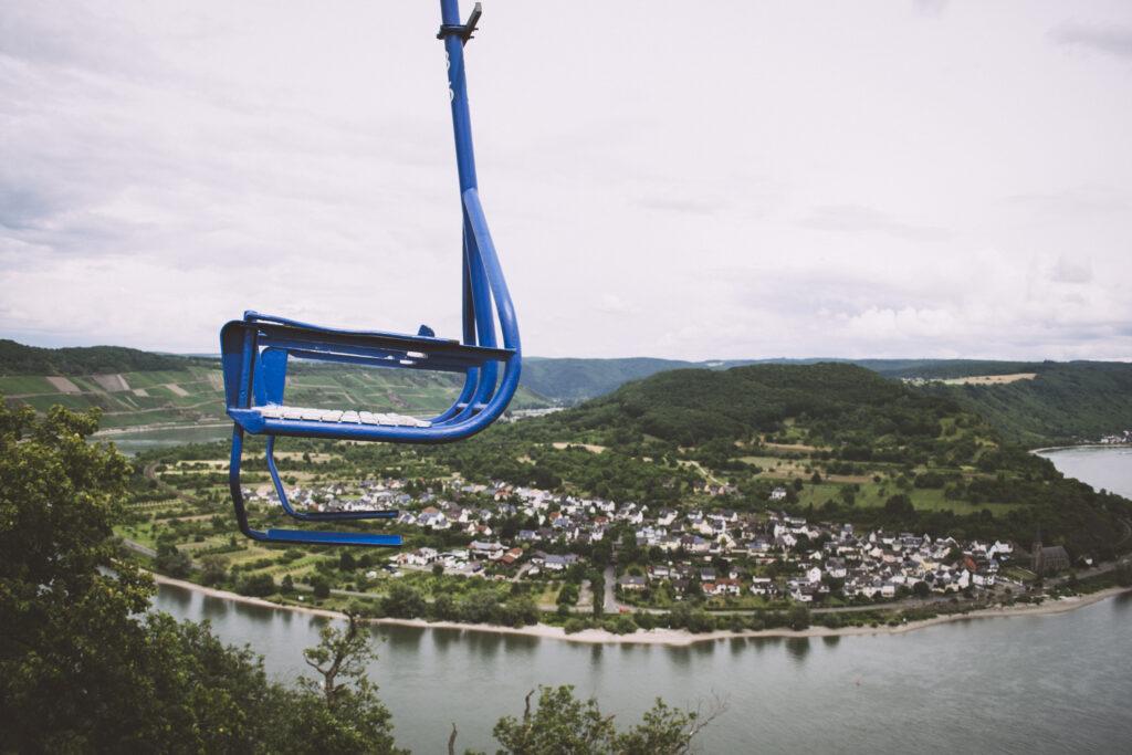 Foto aus dem Sitz der Sesselbahn in Boppard. Im Vordergrund ist ein blauer Sitz, der nach links bergauf fährt, während im Hintergrund die Rheinschleife und der Ort Filsen liegen.